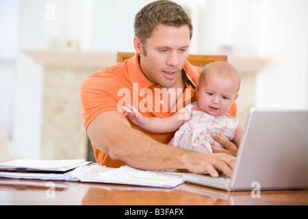 Vater und Baby im Speisesaal mit laptop - Stockfoto