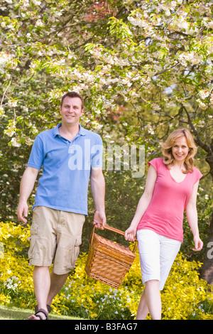 Paare, die im Freien mit Picknick Korb lächelnd - Stockfoto