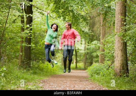 Paar springen auf Weg Hand in Hand und lächelt - Stockfoto