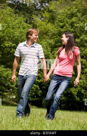 Paar zu Fuß im Freien halten Hände Lächeln - Stockfoto