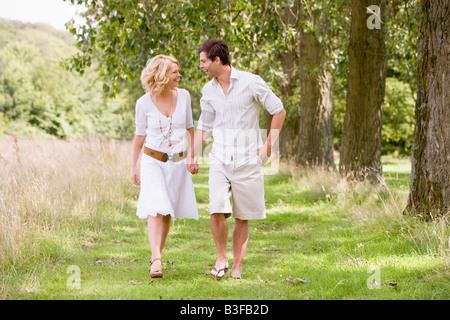 Paar zu Fuß auf Weg halten Hände Lächeln - Stockfoto