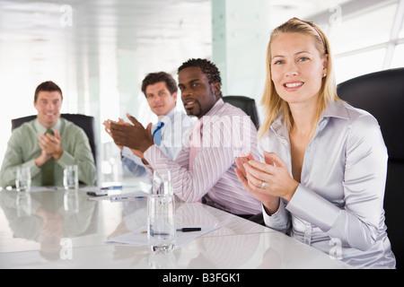 Vier Unternehmer in einem Sitzungssaal applaudieren - Stockfoto