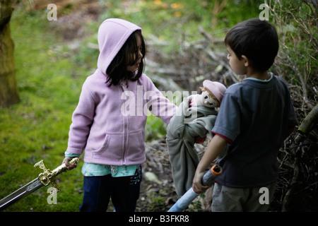 Mädchen im Alter von fünf Jahren beschreibt einen imaginären Feind mit ihrem sechsjährigen Bruder während der Übergabe seiner Spielzeugpuppe