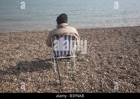 Älterer Mann von hinten tragen Mantel und Hut sitzt im Stuhl am Kiesstrand mit Blick auf das Meer - Stockfoto