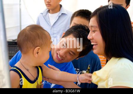 Hmong-Mama und Papa jubeln Sohn nach der Behandlung im Gesundheitswesen-Zelt. Hmong Sport Festival McMurray Feld - Stockfoto