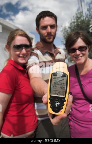 Touristen, die mit einem GPS-Gerät zeigt 00.00.00 Breitengrad auf der Mitte der Erde in der Nähe von Quito in Equador. - Stockfoto