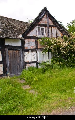 Verlassenen schwarzen und weißen Holz gerahmte Ferienhaus am Straßenrand in Herefordshire, England UK - Stockfoto