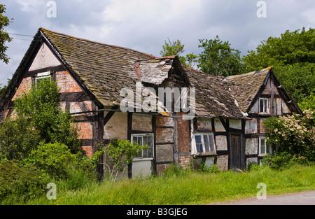 Verlassenen schwarzen und weißen Holz gerahmte Ferienhaus am Straßenrand in Herefordshire - Stockfoto