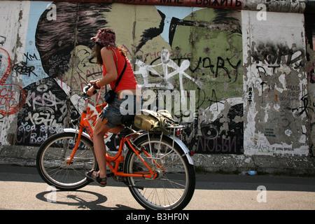 Radfahrer vorbei an Breschnew und Honecker s Kuss abgebildet auf der Berliner Mauer im East Side Gallery in Berlin, - Stockfoto