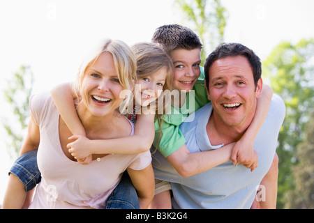 Paar mit zwei kleinen Kindern Huckepack tragen lächelnd - Stockfoto