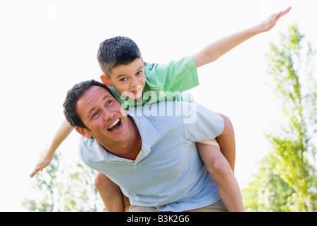 Mann Junge Huckepack Reiten im freien Lächeln - Stockfoto