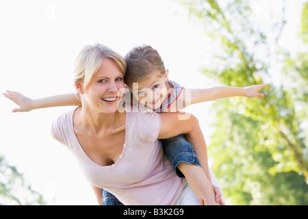 Frau geben junge Mädchen Huckepack Reiten im freien Lächeln - Stockfoto