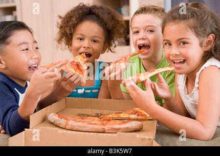 Vier kleine Kinder im Haus Essen Pizza lächelnd - Stockfoto