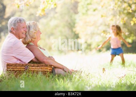 Großeltern bei einem Picknick mit jungen Mädchen im Hintergrund tanzen - Stockfoto