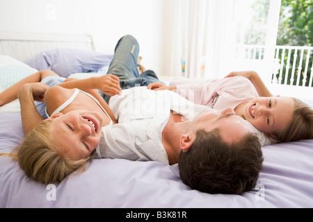 Mann mit zwei jungen Mädchen lächelnd im Bett liegend - Stockfoto