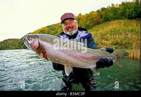 Südwesten ALASKA lächelnd Fischer hält Trophäe Regenbogenforelle fing in der Naknek River in der Nähe von King Salmon - Stockfoto