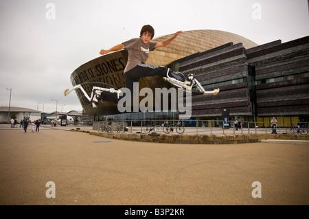 Junger Mann auf bouncy Pogo Stelzen Bockers tun akrobatische Stunts außerhalb des Wales Millennium Centre Cardiff - Stockfoto