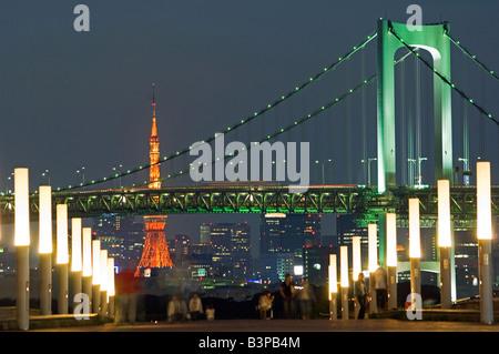 Japan, Tokio, Odaiba. Rainbow Bridge und Tokyo Tower, Menschen in den Vordergrund, wobei einen Abendspaziergang. - Stockfoto