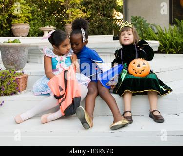 Kleine Mädchen gekleidet wie eine Ballerina und Prinzessin ihre Halloween-Leckereien überprüfen, während die Cheerleaderin - Stockfoto