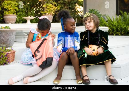 Kleines Mädchen gekleidet wie eine Ballerina prüft ihre Halloween-Leckereien während die Cheerleader und Prinzessin - Stockfoto