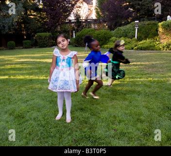 Kleine Mädchen, gekleidet in Halloween-Kostümen führen Sie rund um den Hof. - Stockfoto