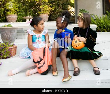 Kleine Mädchen gekleidet wie eine Ballerina und Prinzessin ihre Halloween-Leckereien, überprüfen während die Cheerleaderin - Stockfoto
