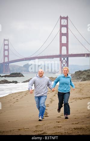 Ein junges Paar Hand in Hand entlang des Strandes vor der Golden Gate Bridge in San Francisco - Stockfoto