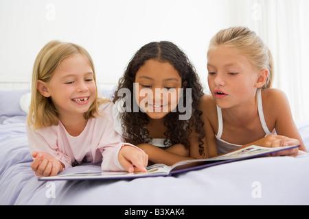 Drei junge Mädchen liegend auf einem Bett im Schlafanzug - Stockfoto