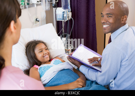 Arzt machen Notizen auf junge Mädchen - Stockfoto