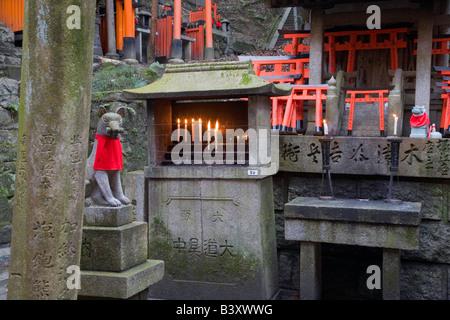 Kyoto-Stadt Japan kleines Torii-Tore und Offertorium Kerzen auf einem Altar des Fushimi Inari Schrein Shinto - Stockfoto