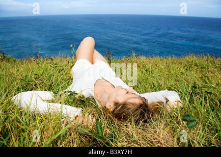 Portrait von junge rothaarige Frau Entspannung in Rasen über dem Ozean in Maui Hawaii - Stockfoto
