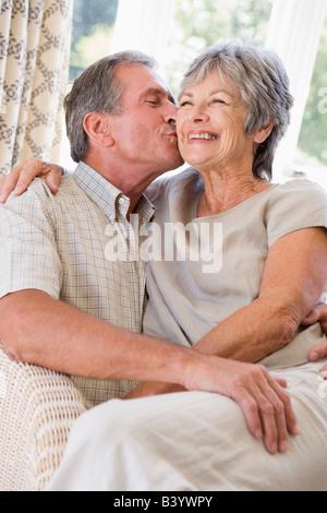 Entspannen im Wohnzimmer küssen und lächelnde paar - Stockfoto