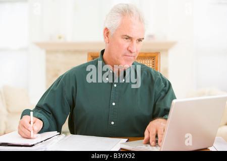 Mann im Speisesaal mit Laptop und Unterlagen - Stockfoto