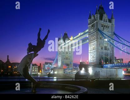 Tower Bridge Nacht Landschaft Stadt Themse London abends beleuchtet mit Statue eines Mädchens und Dolphin Fountain - Stockfoto