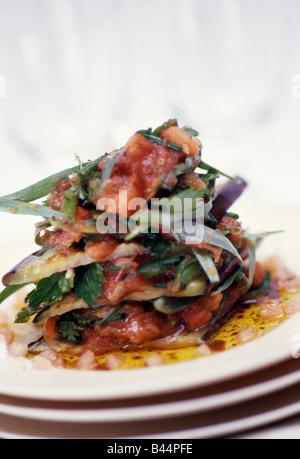 Aubergine Mille-Feuille mit zerdrückten Tomaten und frischen Kräutern - Stockfoto