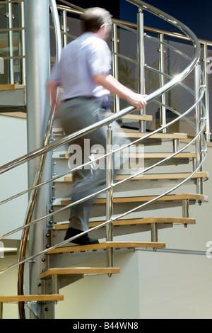 Mann Klettern eine Edelstahl Wendeltreppe in ein modernes Großraumbüro - Stockfoto