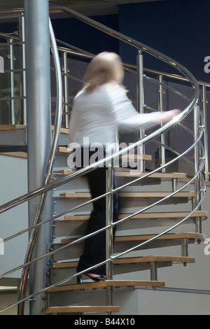 Frau eine Wendeltreppe Edelstahl in ein modernes Großraumbüro Klettern - Stockfoto