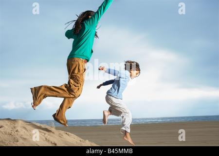 Afrikanischen Brüder springen auf Sanddüne - Stockfoto