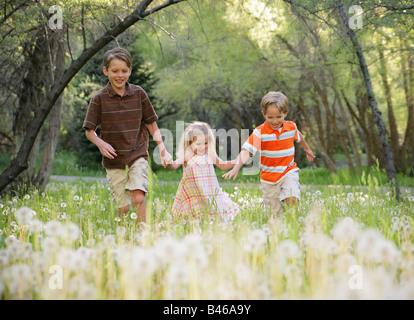 drei Kinder Hand in Hand und zusammen laufen in der Natur - Stockfoto
