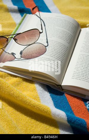 Aufgeschlagene Buch und die Sonnenbrille auf Strandtuch - Stockfoto