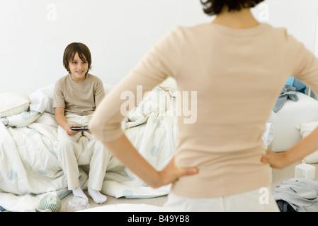 Junge handheld Videospiel in chaotisch Schlafzimmer, Mutter im Vordergrund mit Händen auf den Hüften stehen - Stockfoto