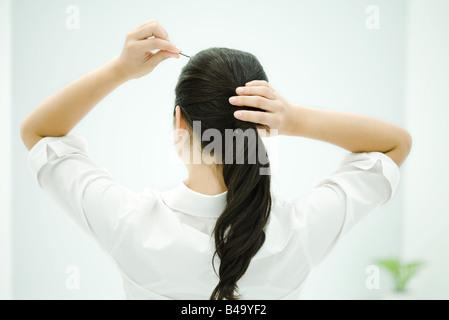 Frau Umsetzung Haare im Pferdeschwanz, Arme angehoben, Rückansicht - Stockfoto