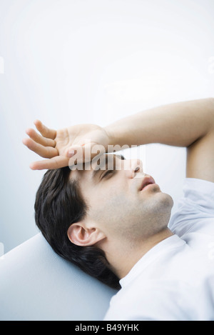 Mann liegend mit geschlossenen Augen, Hand auf Stirn - Stockfoto