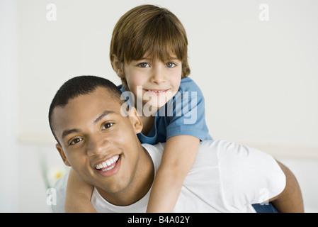 Junger Mann geben junge Huckepack Reiten, beide lächelnd in die Kamera - Stockfoto