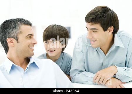 Vater und zwei Söhne, die lächelnd an einander, Nahaufnahme - Stockfoto
