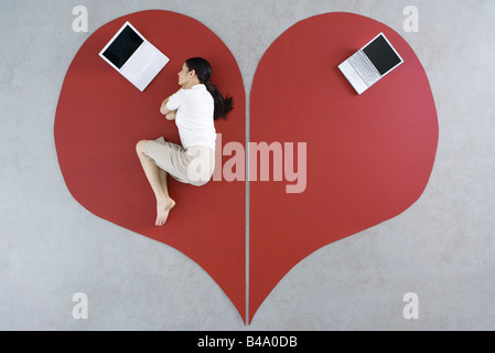Frau auf dem Boden liegend mit Laptop auf großen Liebeskummer, verlassen Laptop hinter ihr - Stockfoto