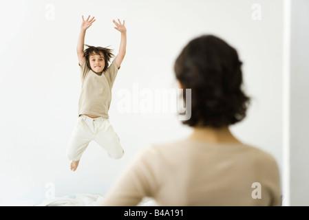 Junge, springen auf Bett, Mutter, die gerade aus der Tür - Stockfoto