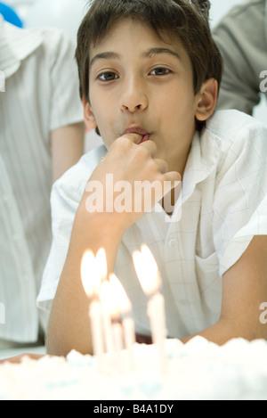 Junge vor Geburtstagstorte mit Kerzen, Zuckerguss mit Finger Verkostung - Stockfoto