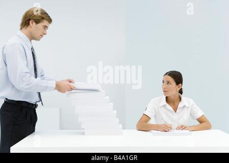 Mann zu großen Stapel von Dokumenten auf berufstätige Frau Schreibtisch hinzufügen - Stockfoto