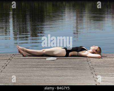 Eine Frau in einem Badeanzug liegen auf einem Steg - Stockfoto